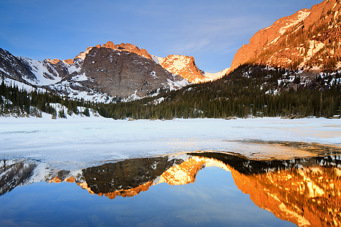 Rocky Mountain National Park's Cathedral Wall and Taylor Peak catch the first rays of Sun as they reflect in a mostly frozen Loch.