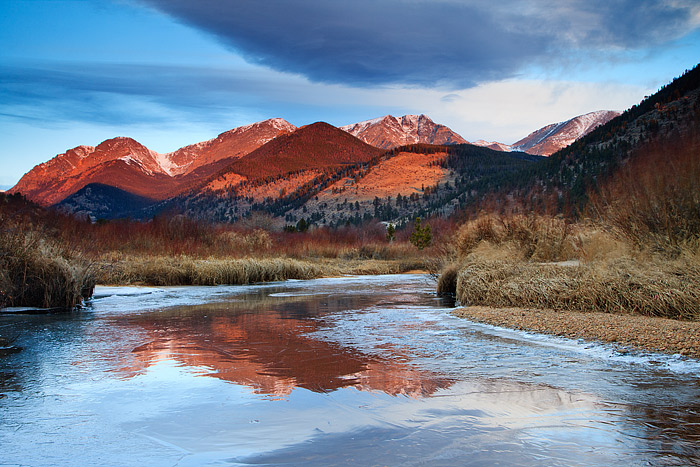 The Mummy Range reflected in the frozen water of Fall River, Rocky Mountain National Park
