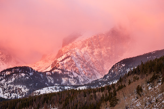 Hallet Peak basks in the warm light of sunrise as snow and wind blow over the peak. Hallet Peak is one of the most recognizable features in Rocky Mountain National Park. Hallet make for a great subject for photography in the park. Technical Details: Canon EOS 1Ds III, 70-300mm F4-5.6 L