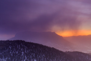 Wind blown snow flies across the horizon and over Deer Mountain as the orange pre dawn glow of sunrise begins to light the sky over Rocky Mountain National Park. Technical Details: Canon EOS 5D Mark III, 24-70mm F4 IS