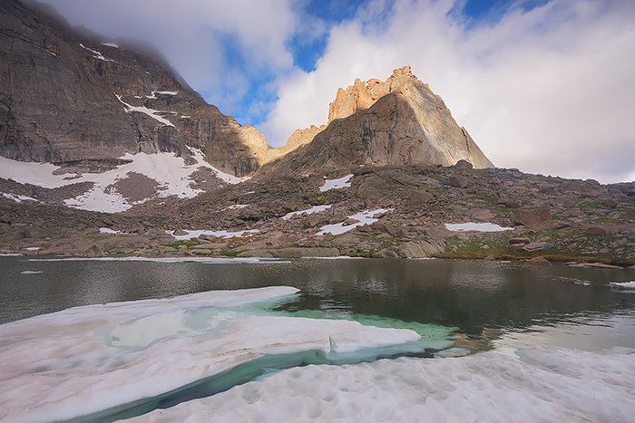 It was July 10th at Green Lake deep within the backcountry of Glacier Gorge but the lake still has yet to completely thaw out. The Spearhead formation rises above Green Lake as clouds streak above and over this famous formation. Technical Details: Nikon D810, Nikkor 16-35mm F4 VR