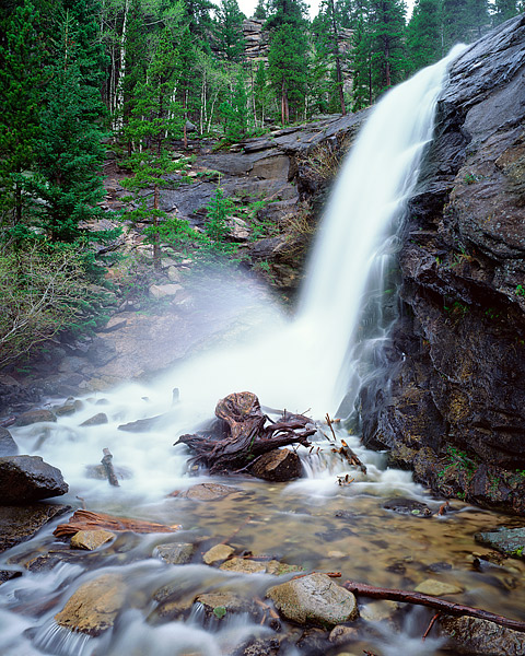 Cow Creek tumbles 20 feet over the granite and rock that forms Bridal Veil Falls in Rocky Mountain National Park. Rain and mist...