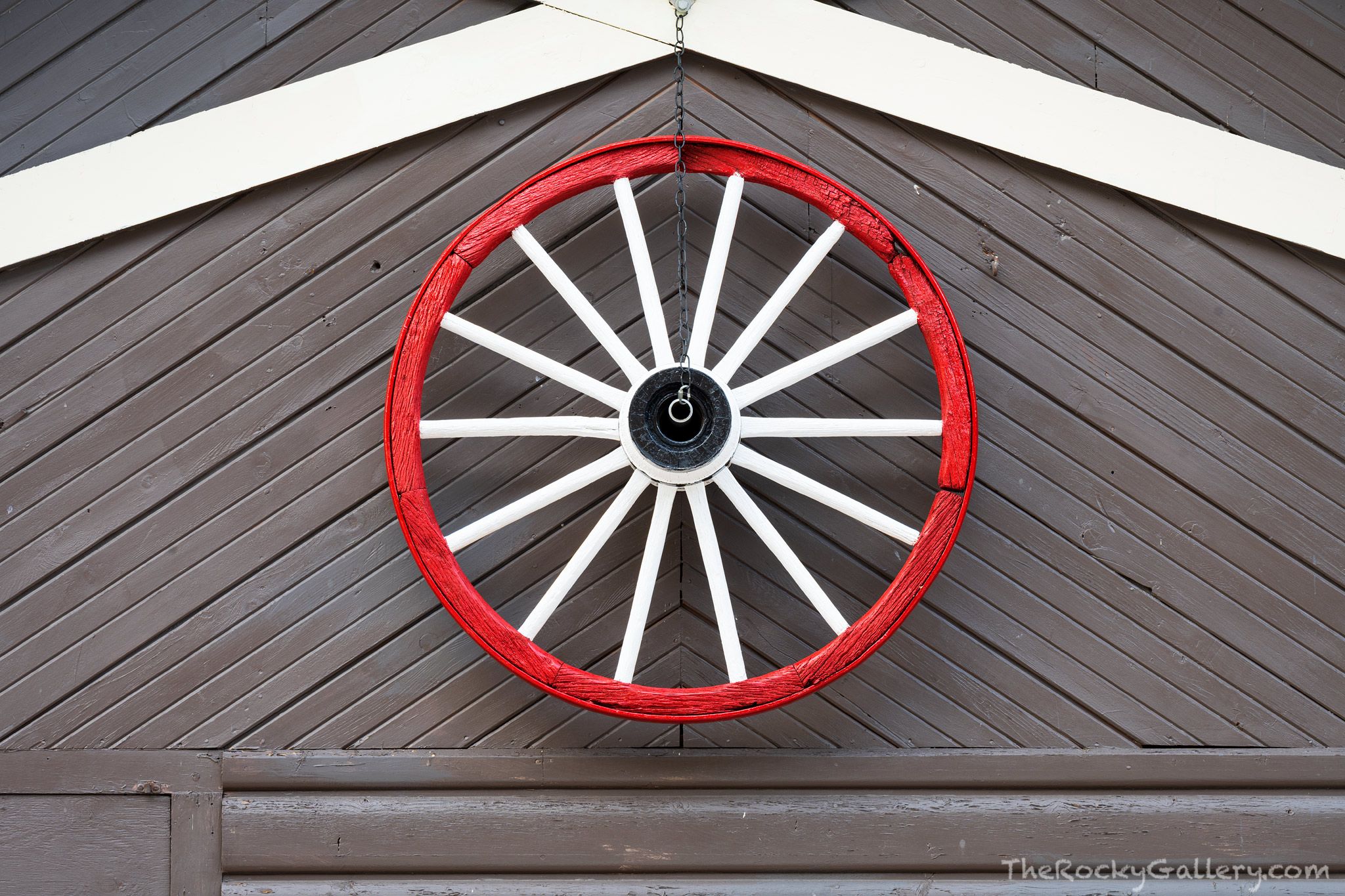A clapboard wagon wheel hangs on the side of the Gateway Grocery store just outside the Fall River Entry to Rocky Mountain National...