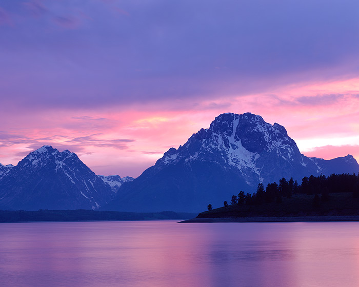 The Sun is setting behind Wyoming's Grand Teton Mountain Range and Mt. Moran. Afternoon Thunderstorms raked over Jackson Lake...