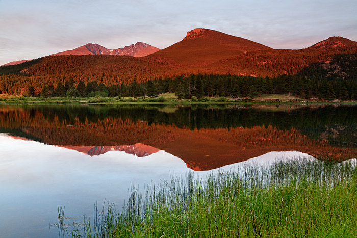 The reflections of Longs Peak, Mount Meeker and the Estes Cone glow on the placid surface of Rocky Mountain National Park's Lily...