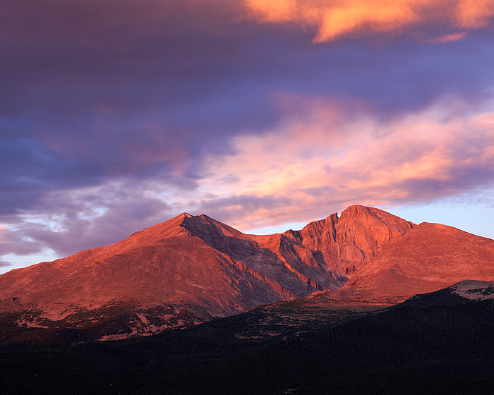 A brilliant magenta and red sunrise illuminates Longs Peak and Mount Meeker from the Twin Sisters. It's a serene and windless...