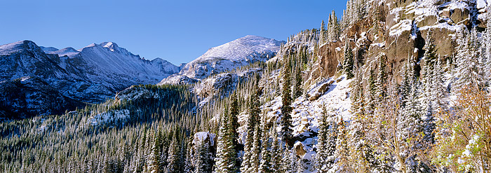 Longs Peak shines in the distance after a being coated by an early season snowstorm. Fall in Rocky Mountain National Park is...
