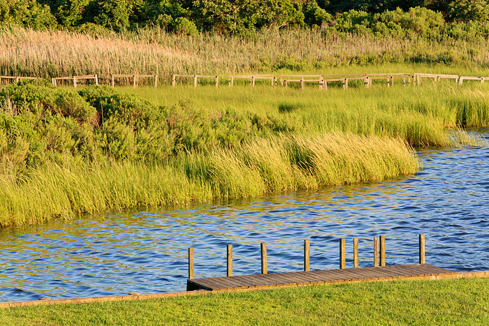 High tide rolls in along the shores and docks of Old Fort Pond in Southampton, New York after another glorious day in the Hamptons...