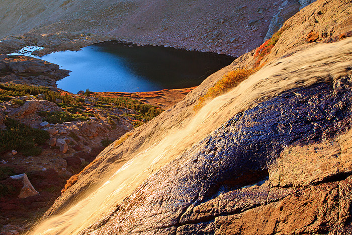 The alpine tundra in Rocky Mountain National Park has turned a brilliant red and orange hue. The deep blue of Peacock Pool...