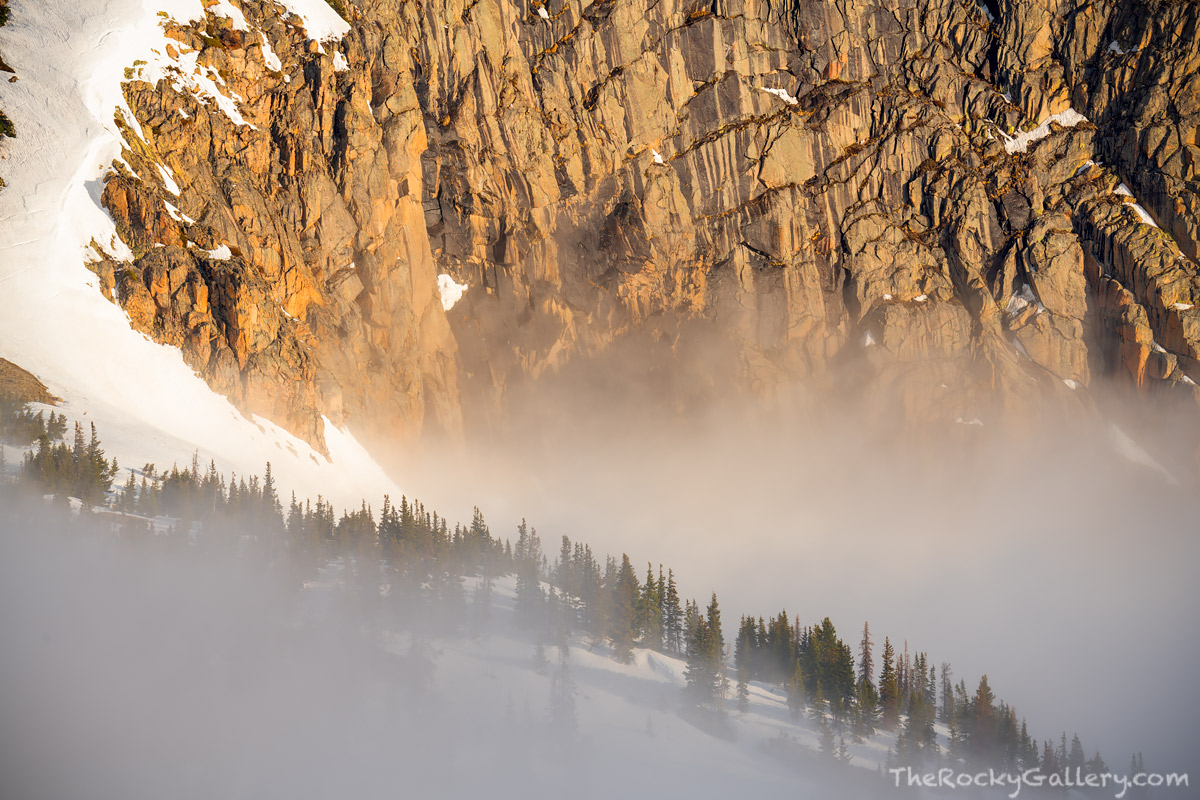 The eastern flank of Sundance Mountain glows in the mornings first light as fog lifts from Hanging Valley below.