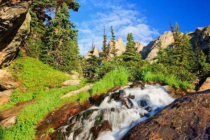 Tydall Falls cascades through the pines between Emerald Lakeand Dream Lake in Rocky Mountain National Park. Mountain Blue...
