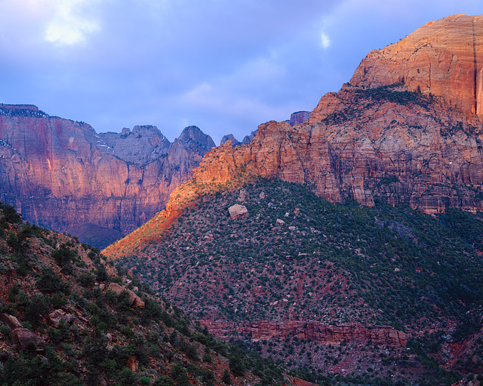 The sunrise breifly shines through the thick cloud cover over Zion National Park. The lighting, although brief helps highlight...